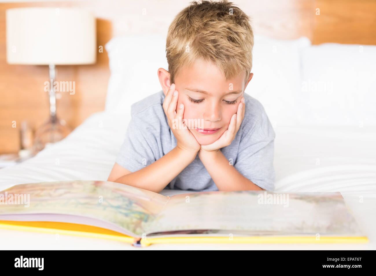 Happy blonde boy lying on bed reading a storybook - Stock Image