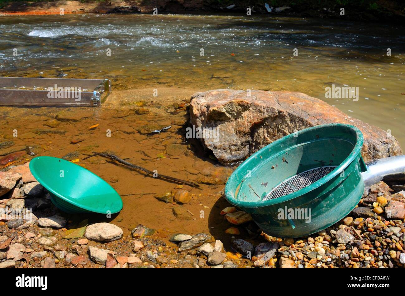 Panning for gold with a sluice box, sifter and pan, set up in the river - Stock Image