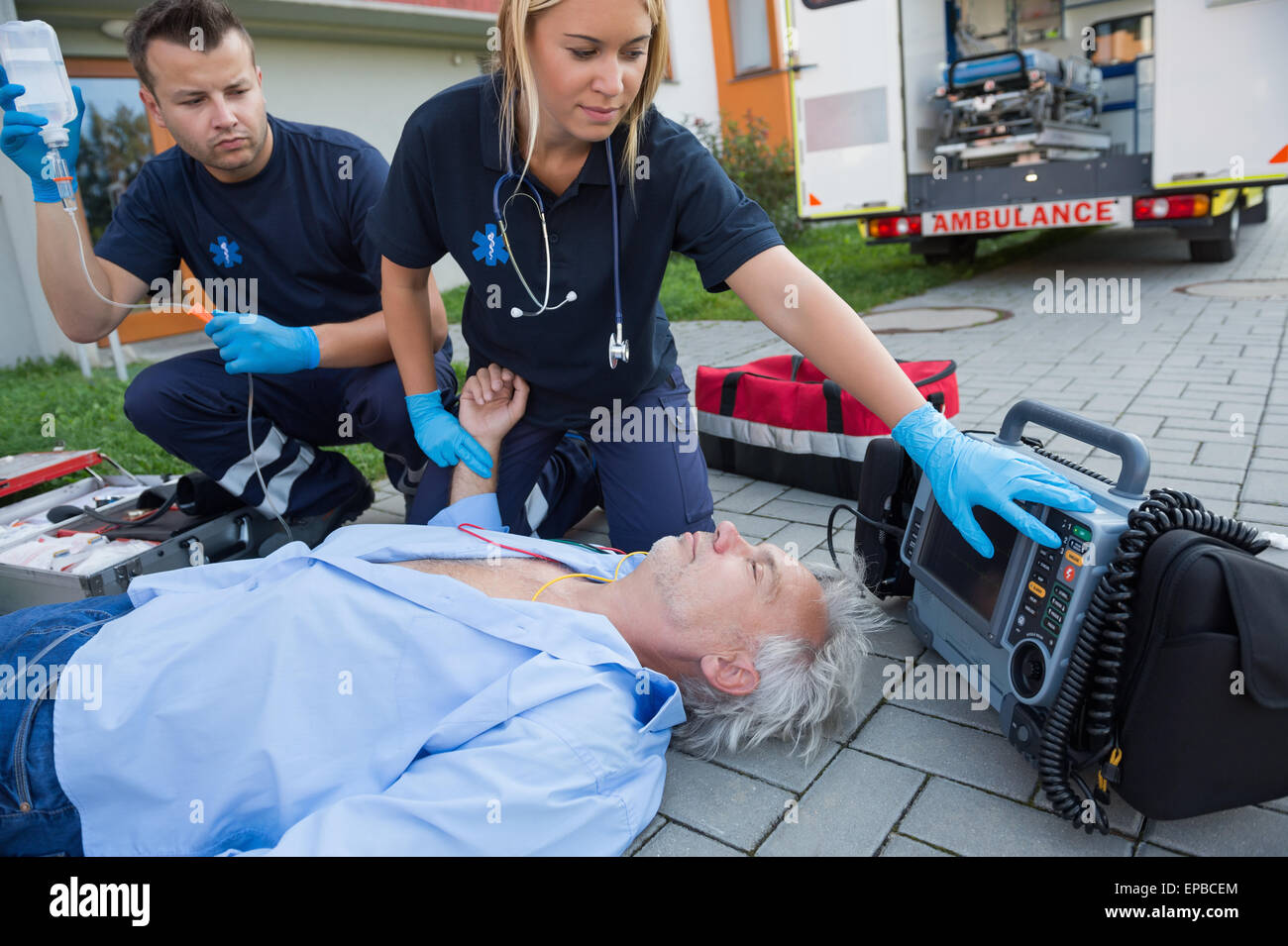 Paramedics checking pulse of unconscious man - Stock Image