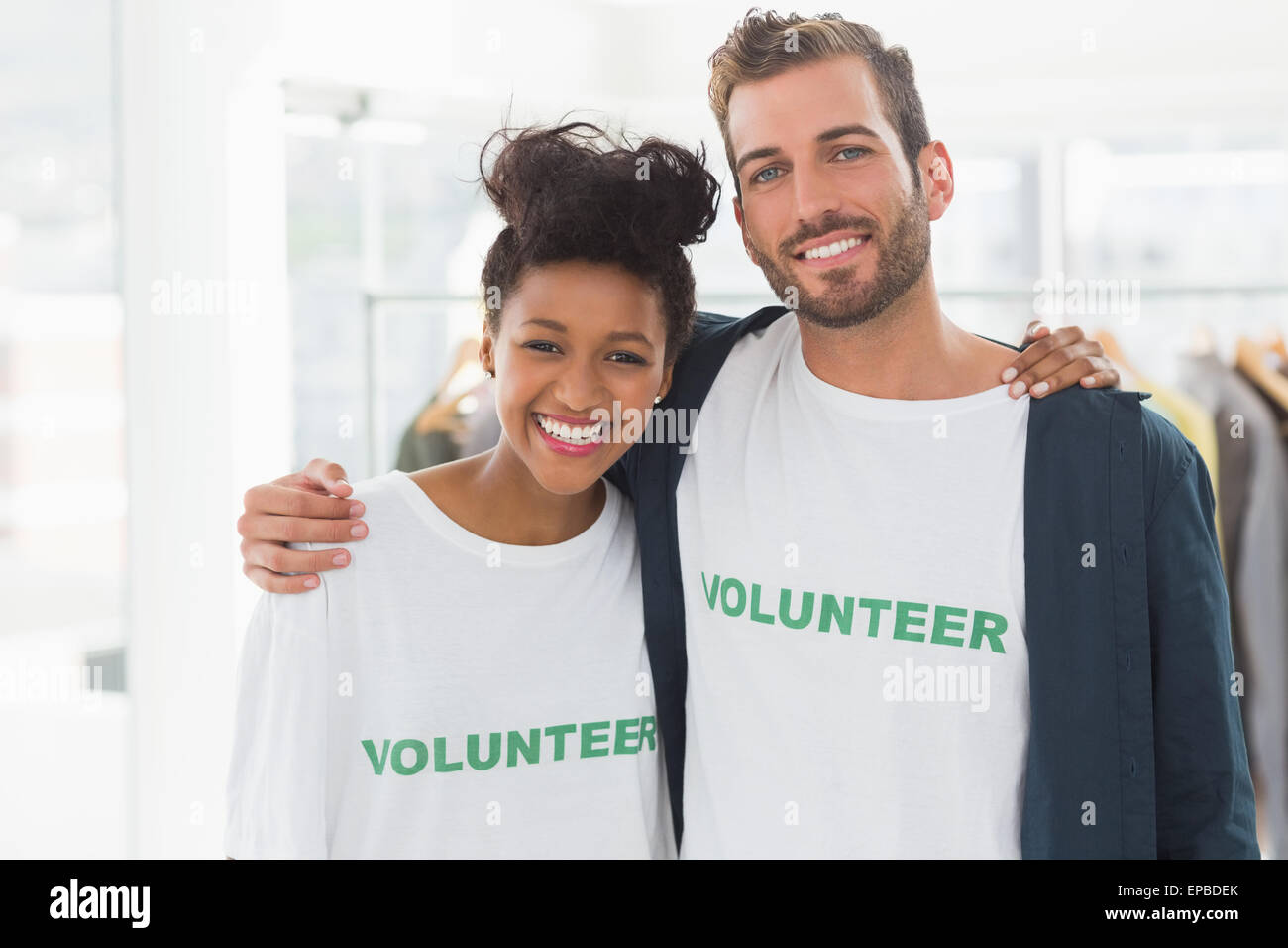 Portrait of two young volunteers with arms around - Stock Image