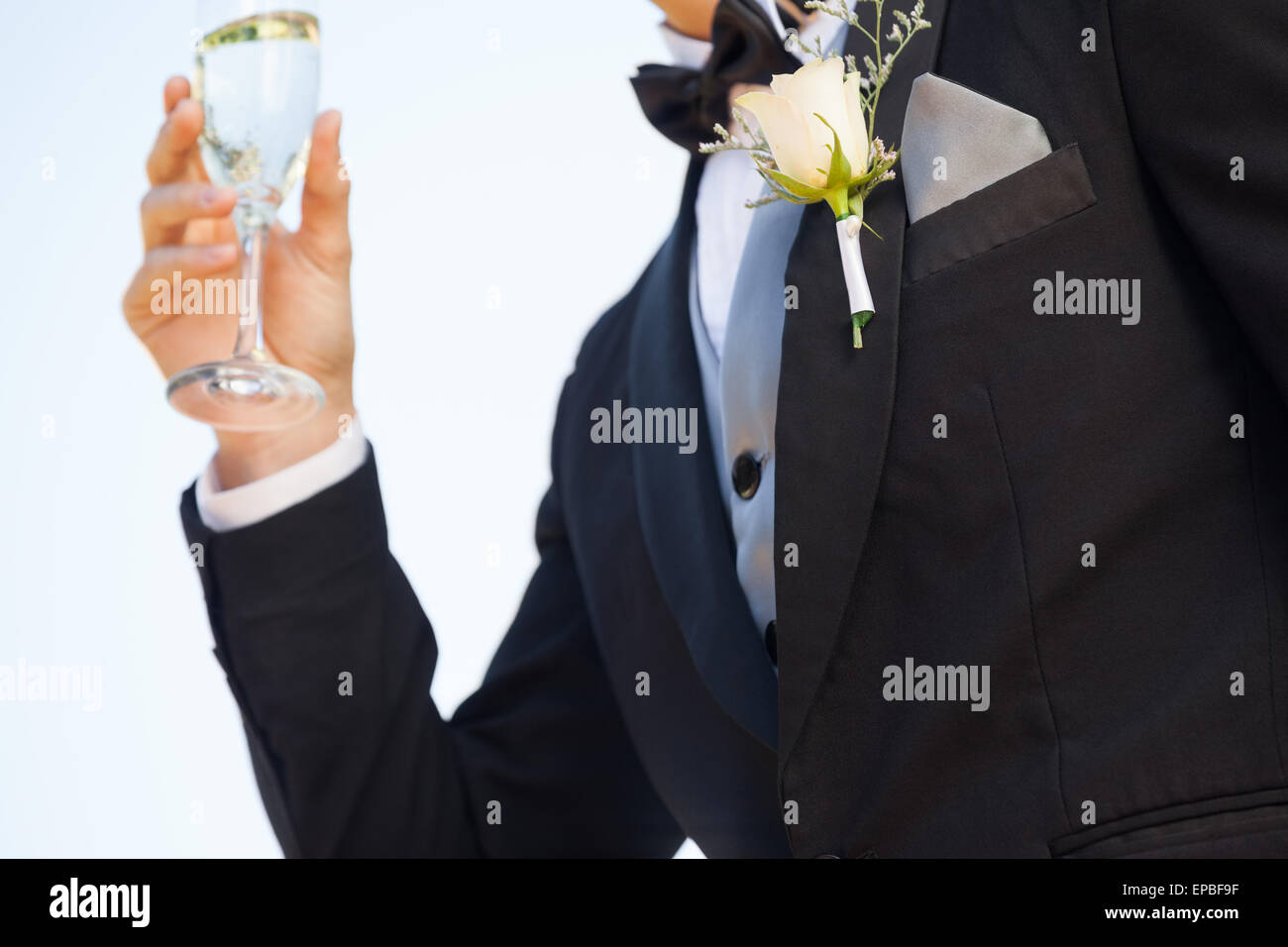 Mid section of flowers on lapel of male as he holds champagne glass Stock Photo