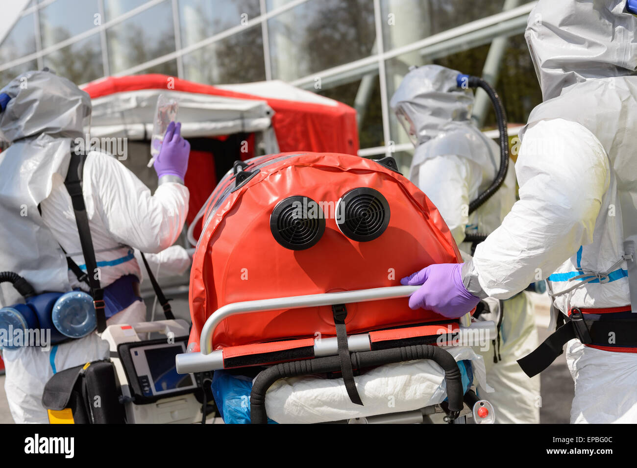 Biohazard team pushing stretcher towards chamber - Stock Image