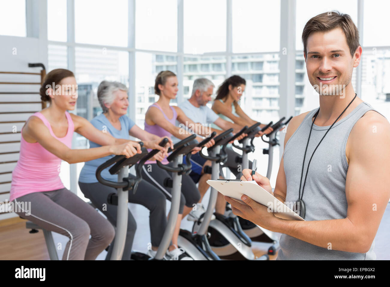Trainer with people working out at spinning class - Stock Image