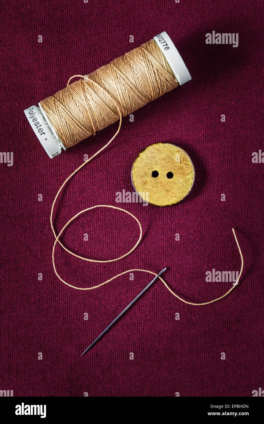 Close up of thread, button and needle - Stock Image