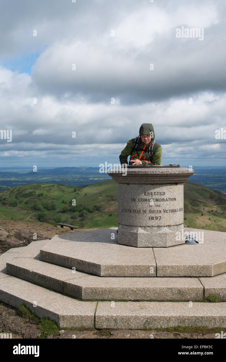 Man studying map on the Victoria memorial on top of the Worcester Beacon Malvern Hills, Worcestershire, England, - Stock Image