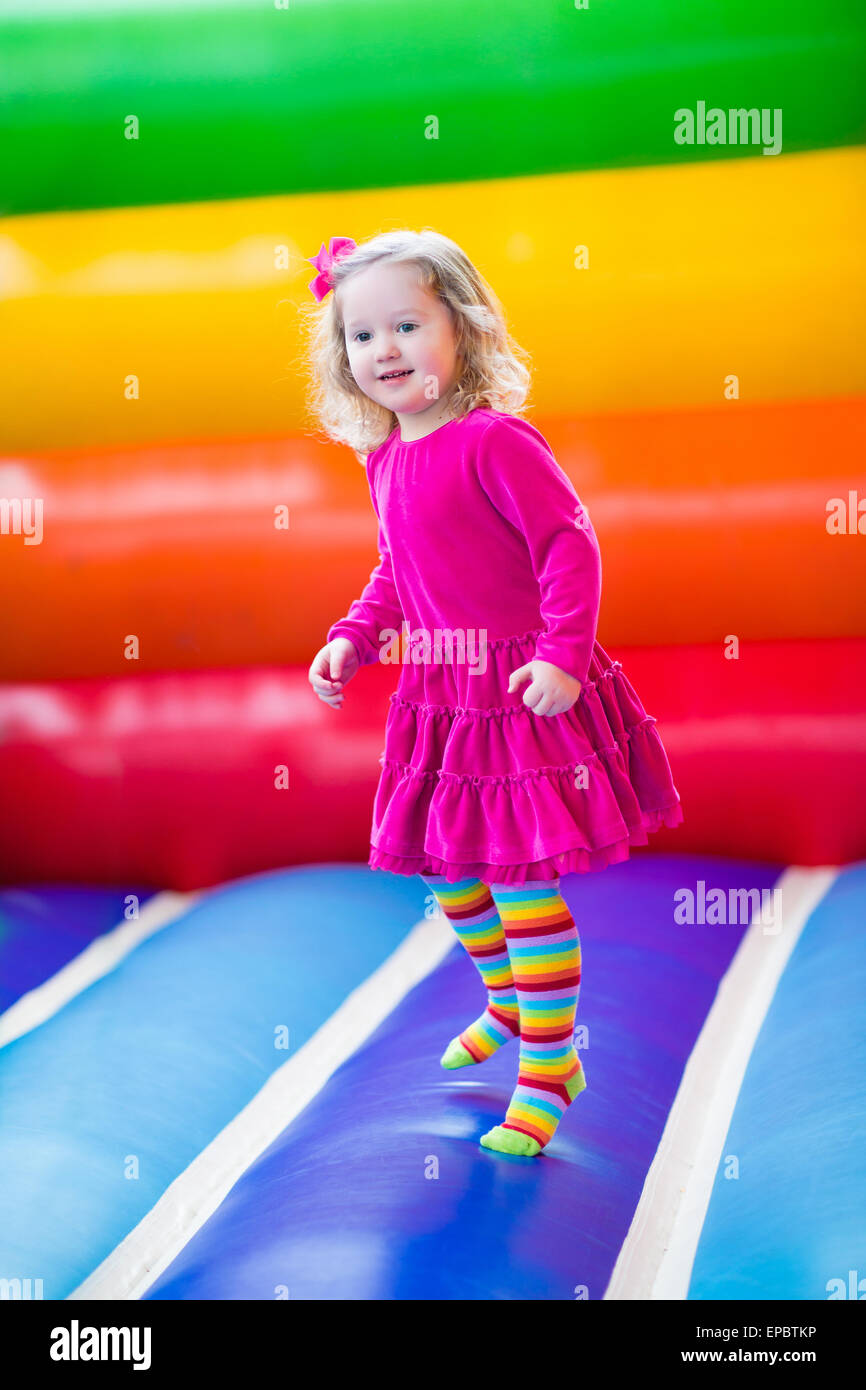 Cute funny preschool little girl playing, jumping and bouncing in an inflatable castle at birthday party on a kids - Stock Image