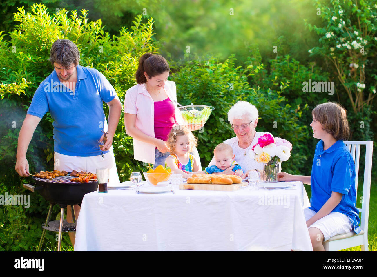 Grill barbecue backyard party. Happy big family enjoying BBQ lunch with grandmother eating grilled meat in the garden - Stock Image