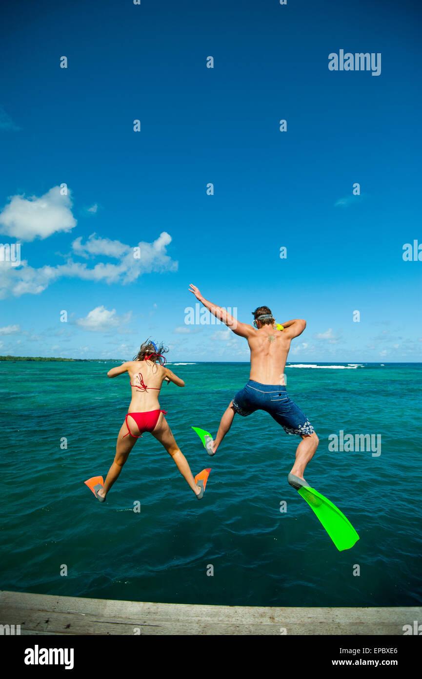 Snorkellers jumping into the waters off Uplulu Island; Upulu, Samoa Stock Photo