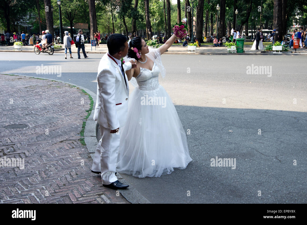Bride and groom being photographed on street - Stock Image