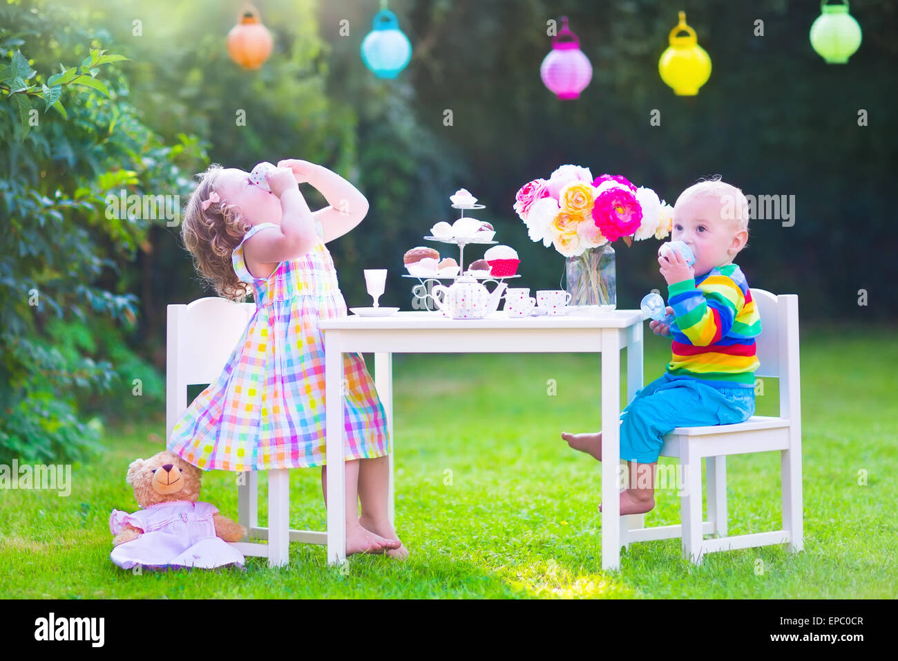 Two happy children, cute curly toddler girl and a little baby boy, brother and sister, enjoying a tea party with - Stock Image