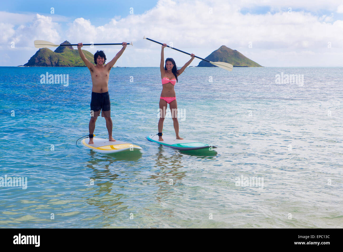 japanese couple on stand up paddleboards in hawaii Stock Photo