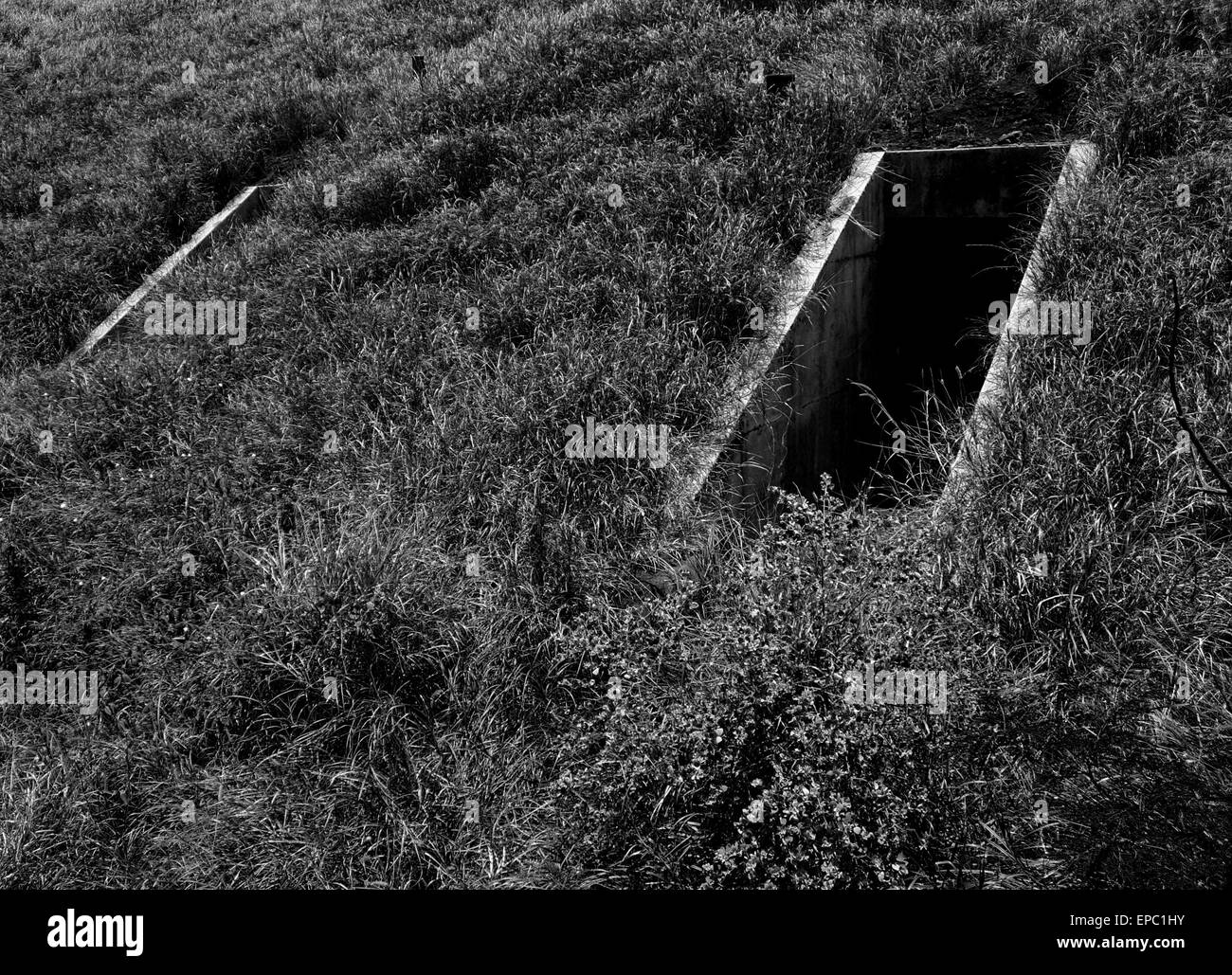 Entrances to WW-II ammo bunkers at an airfield. - Stock Image