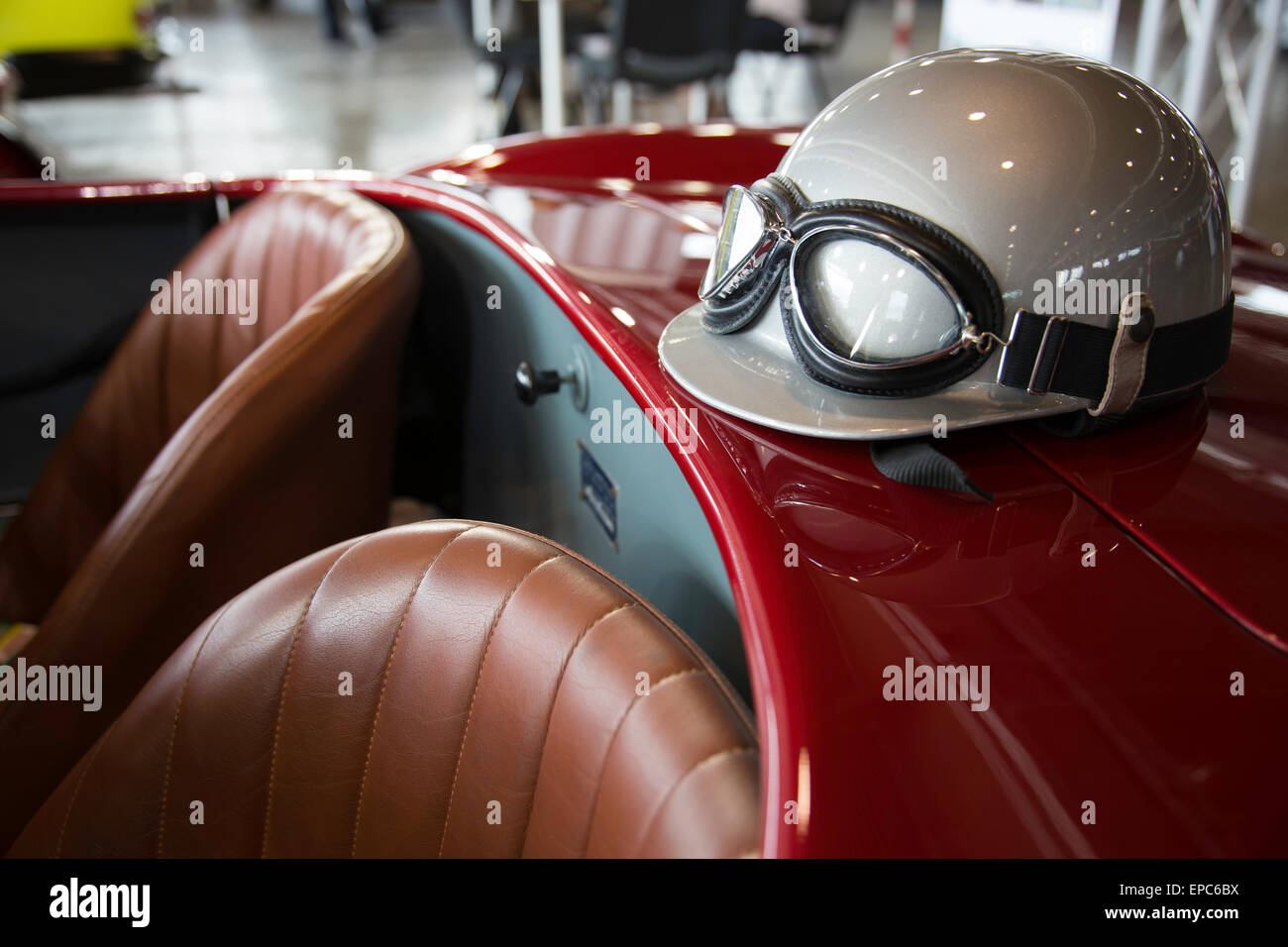 helmet and glasses resting on a luxury convertible sports car - Stock Image