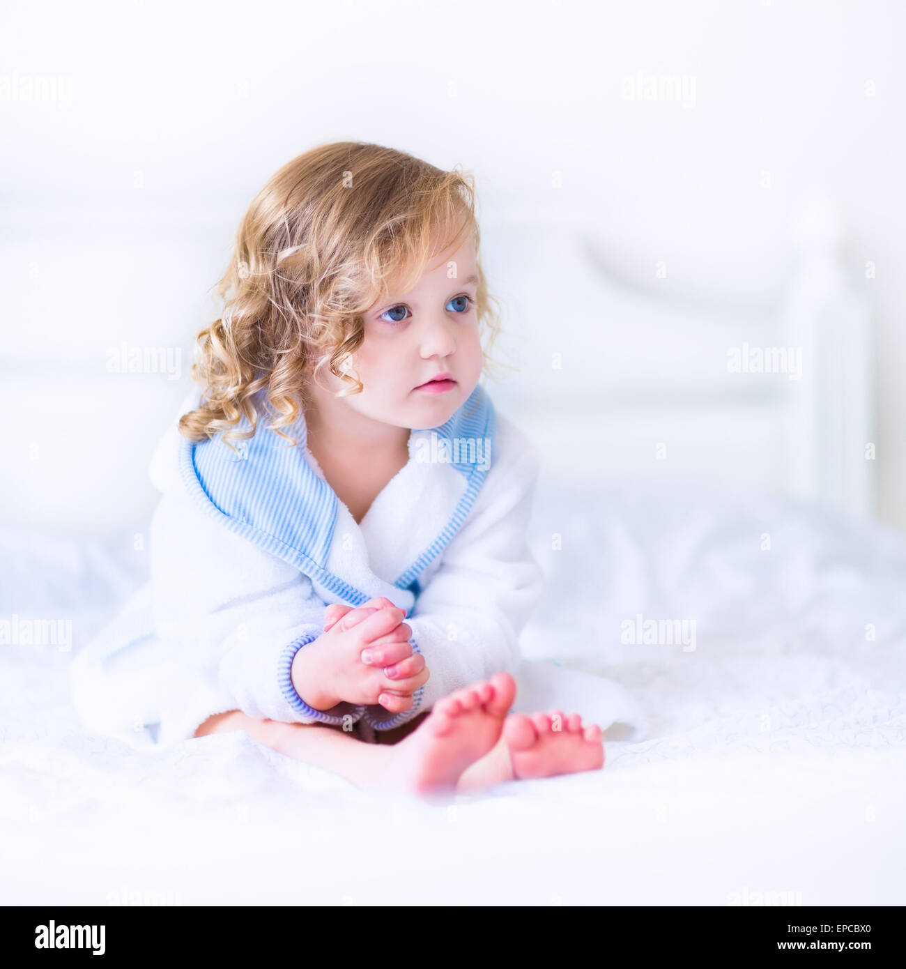 Cute curly little girl in a white and blue bathrobe with a towel over her wet hair siting in a sunny bedroom after - Stock Image