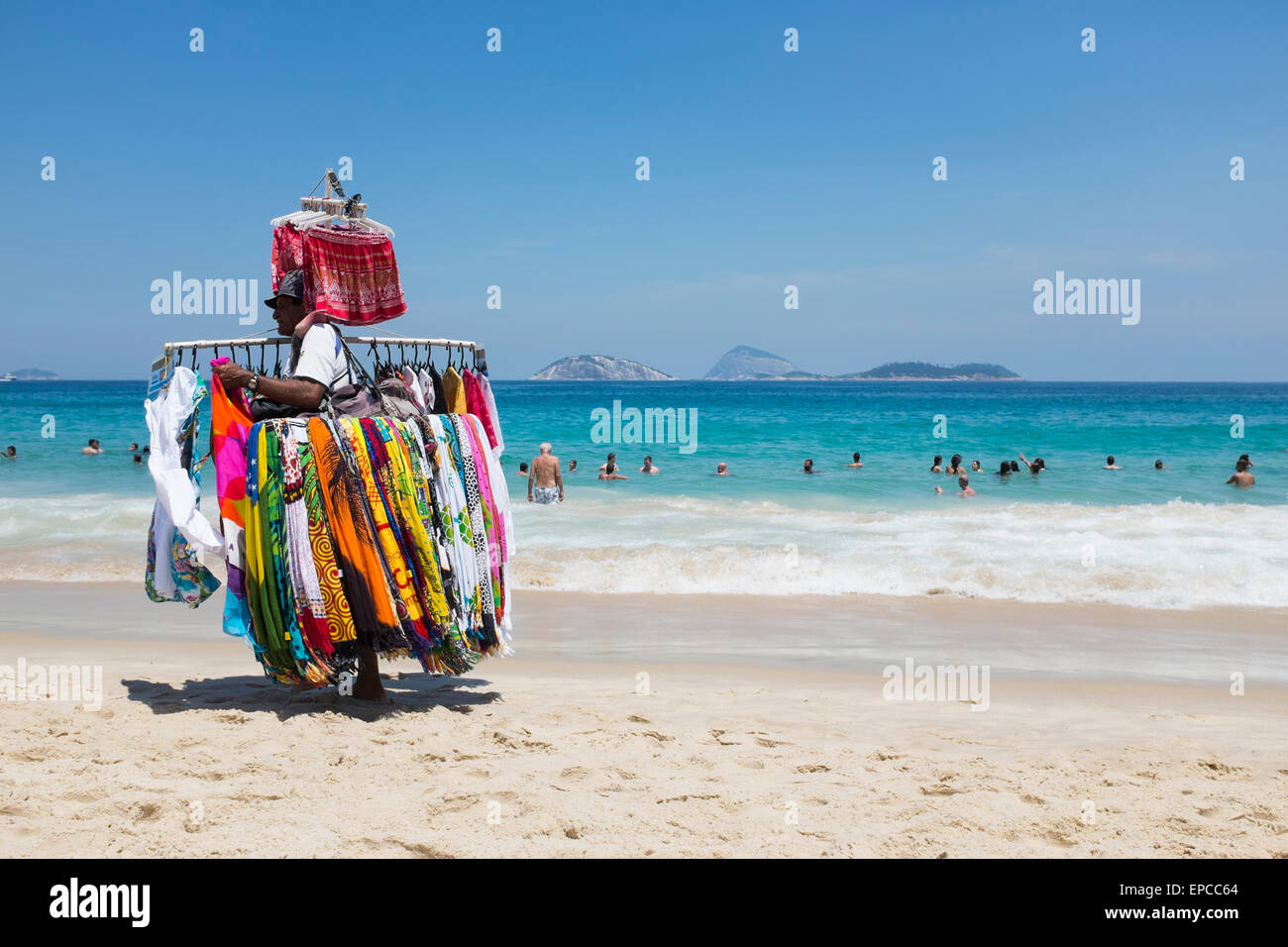 RIO DE JANEIRO, BRAZIL - MARCH 15, 2015: A beach vendor selling brightly colored dresses carries merchandise on - Stock Image
