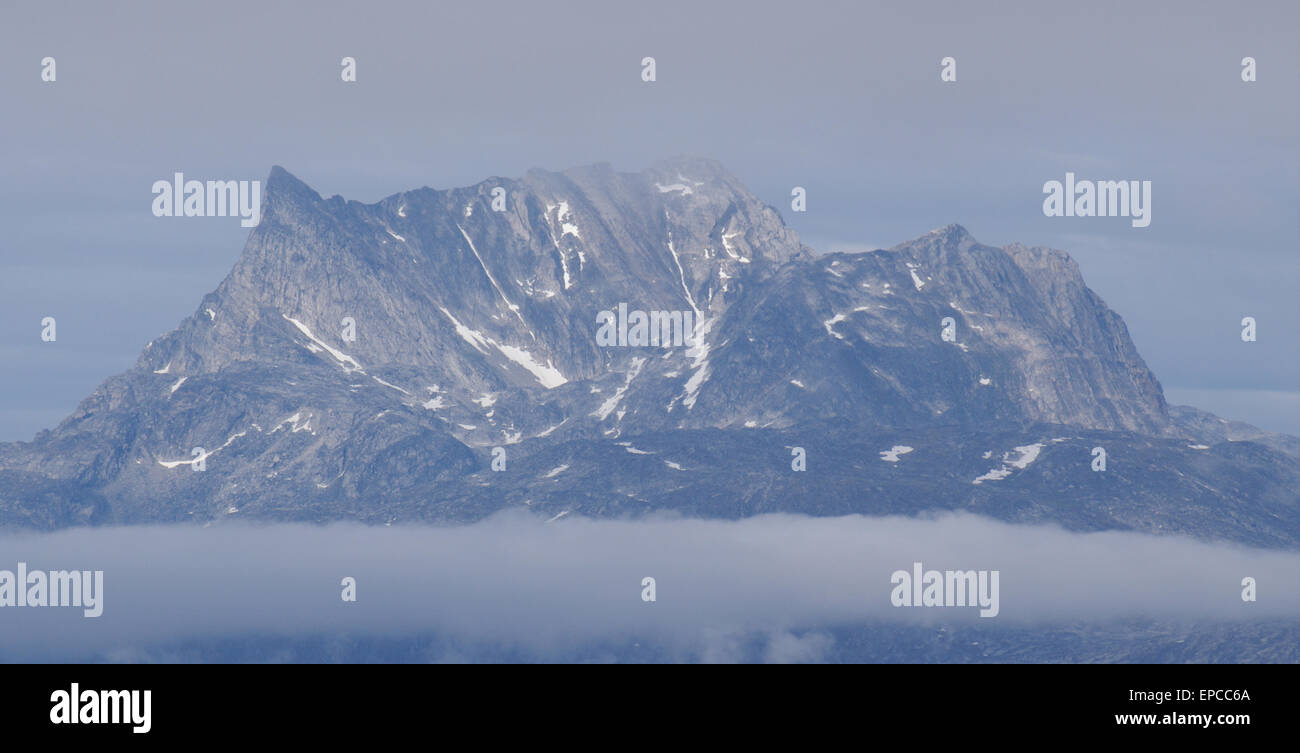 Snow capped mountains emerge from mist - Stock Image