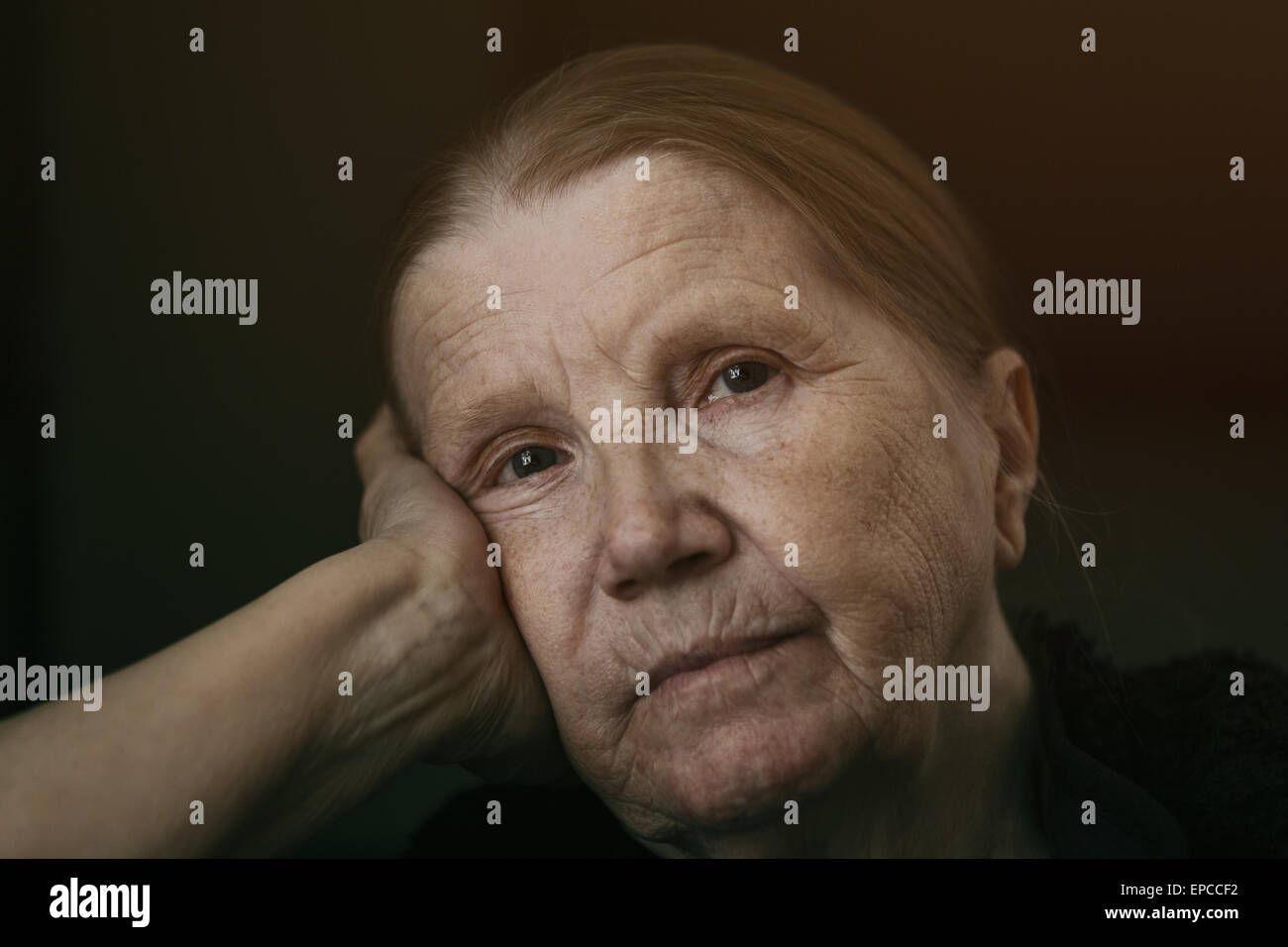senior woman looking to the camera with sad look shalow DOF - Stock Image