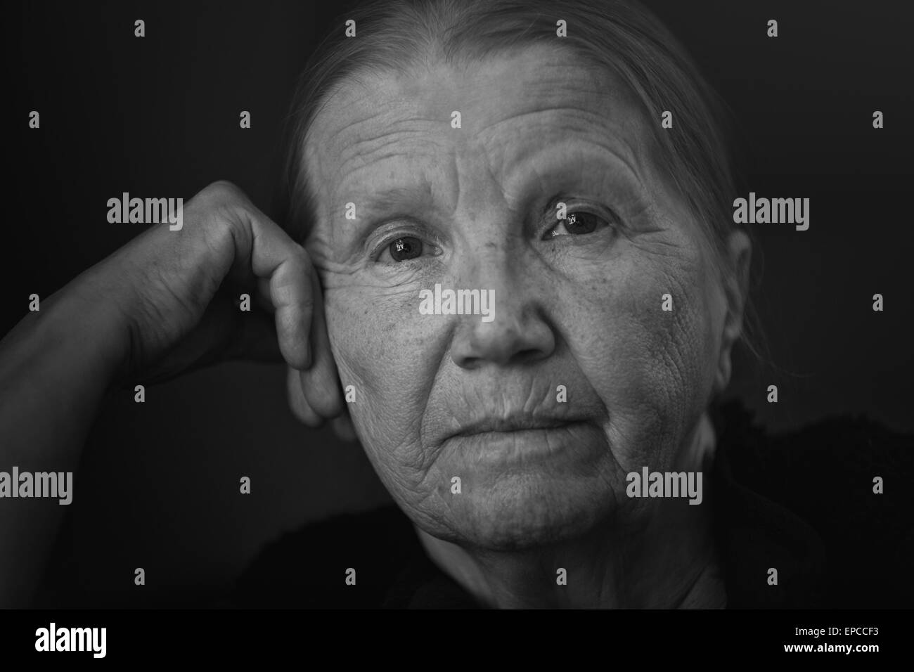 senior woman looking to the camera with shalow DOF - Stock Image