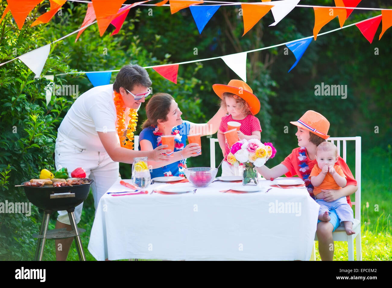 Happy big Dutch family with kids celebrating a national holiday or sport victory having fun at a grill party in - Stock Image