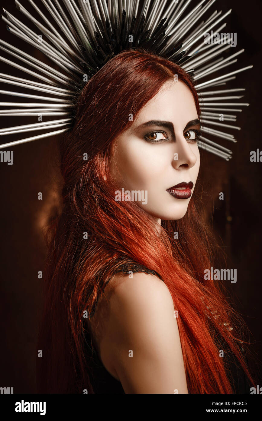 Closeup portrait of a beautiful gothic girl wearing spiked headgear - Stock Image