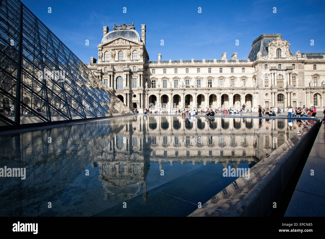 Tourists congregate near a reflecting pool in the inner courtyard at the Louvre.  Paris, France. - Stock Image