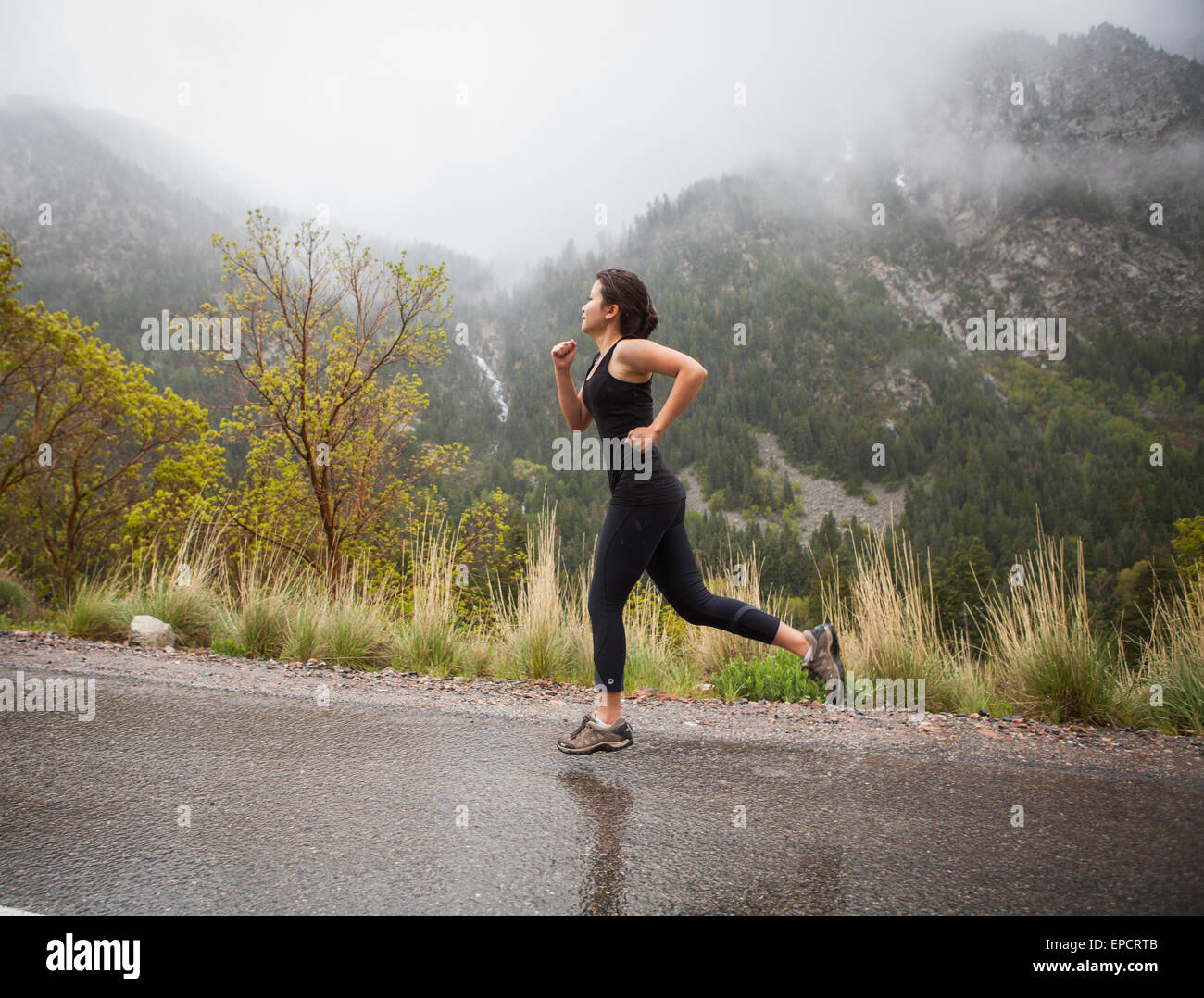 woman running in the rain on road in mountains - Stock Image