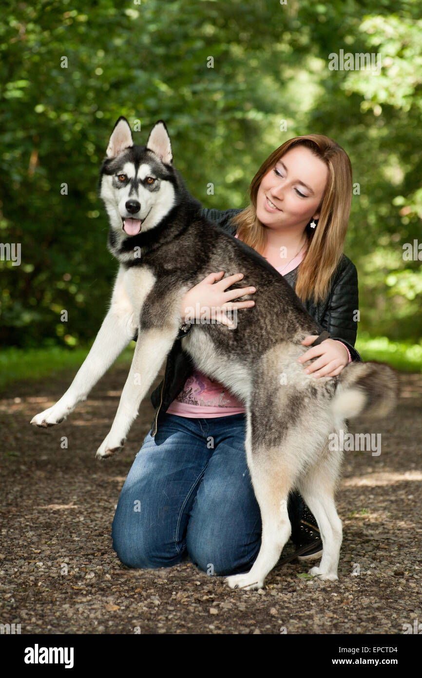 Young woman and her husky in the forest - Stock Image