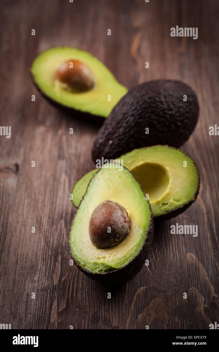 Avocado on wooden table - Stock Image