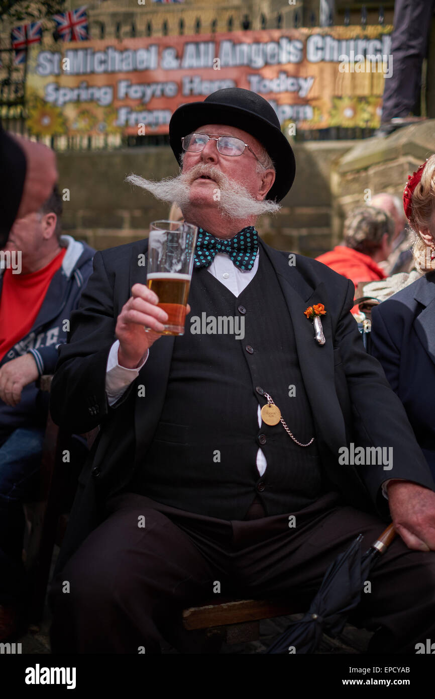 Old city banker dressed up with large mustache, bow-tie and pint of beer - Stock Image