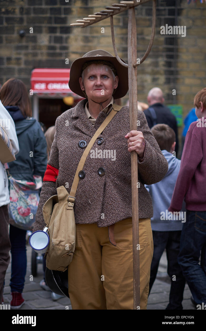 Woman dressed up as WW2 land worker with rake - Stock Image