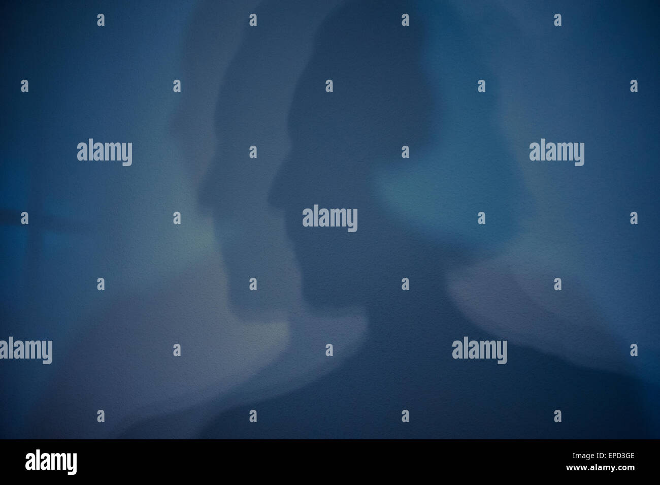 Silhouetted faces projected on wall multiple personality disorder - Stock Image