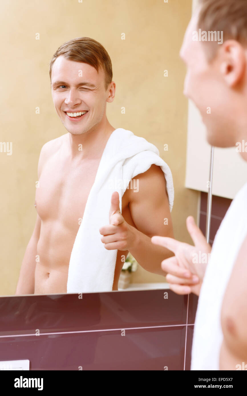 Man giving himself wink I front of mirror Stock Photo
