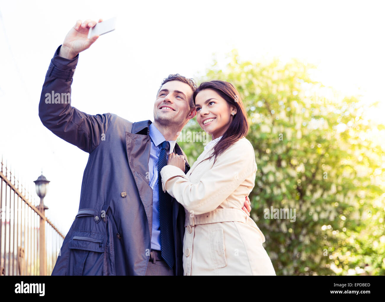 Happy young couple making selfie photo on smartphone outdoors Stock Photo