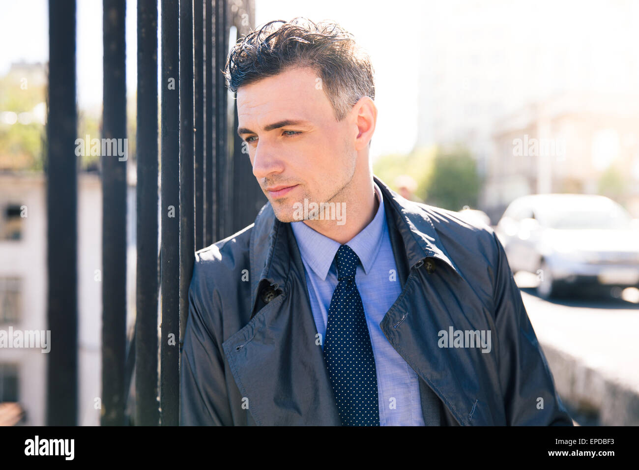 Portrait of a pensive businessman looking away. Standing outdoors - Stock Image