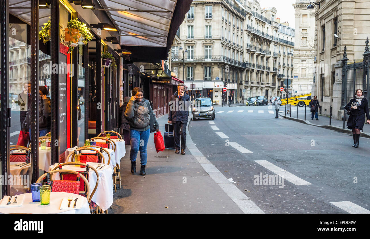 Paris restaurant with sidewalk tables and chairs for alfresco dining - Stock Image
