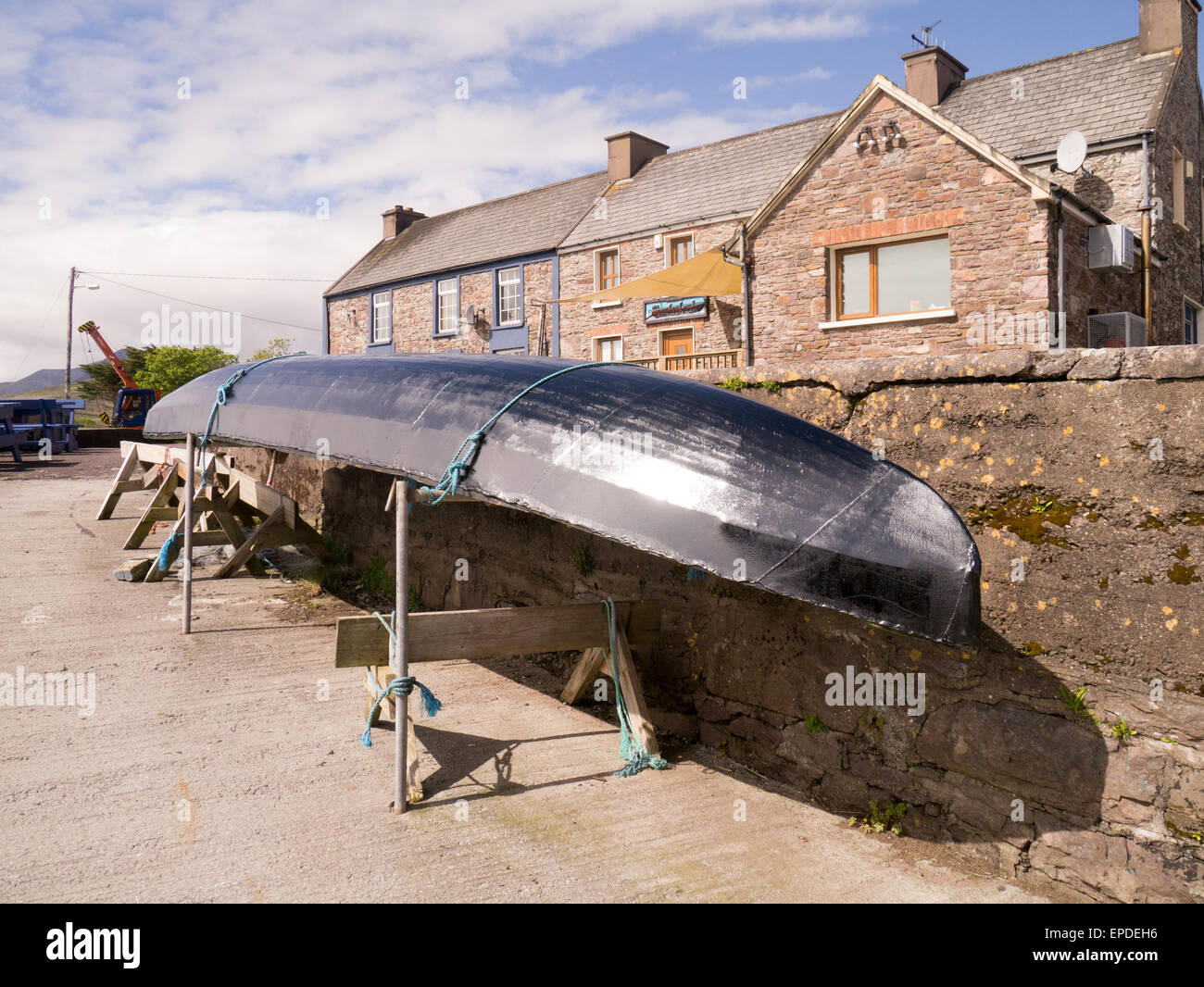 A curragh, a traditional fishing boat on Brandon Pier on the Dingle Peninsular,County Kerry on the Wild Atlantic Stock Photo