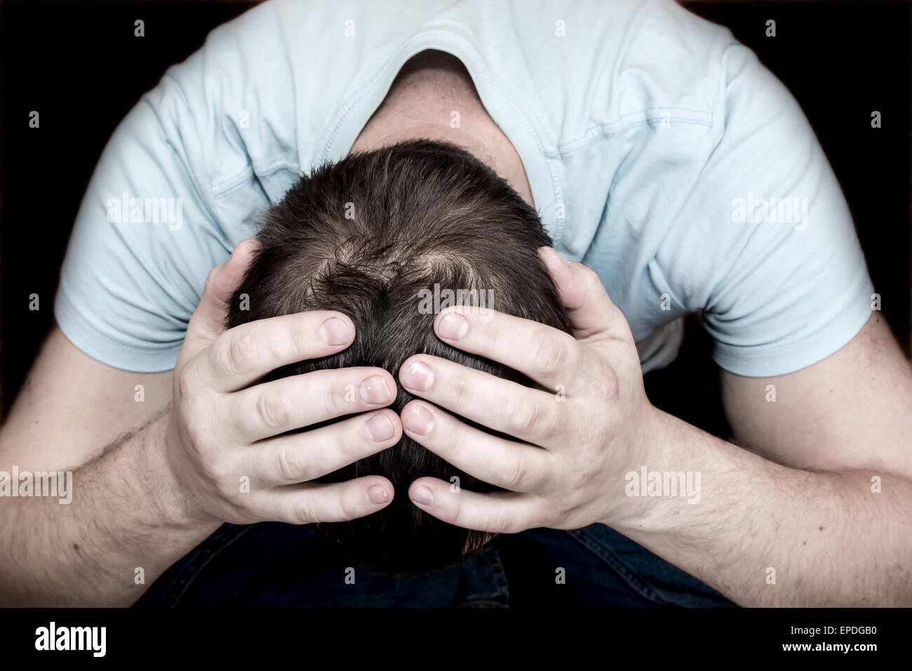 Depressed crying scared man holding his head in his hands sitting on floor over black background. Despair, depression, - Stock Image