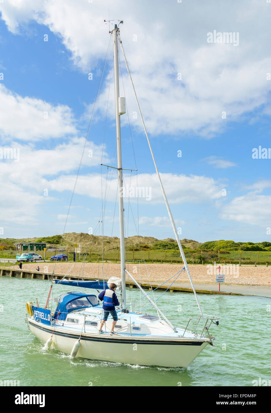 Small yacht on the river without a sail up. - Stock Image