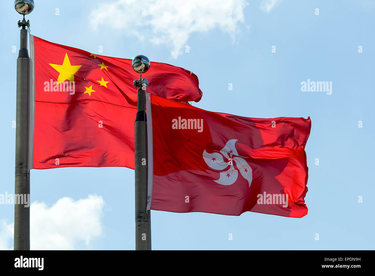 Hong Kong and Peoples Republic of China Flags Flying Side by Side Against Blue Sky - Stock Image