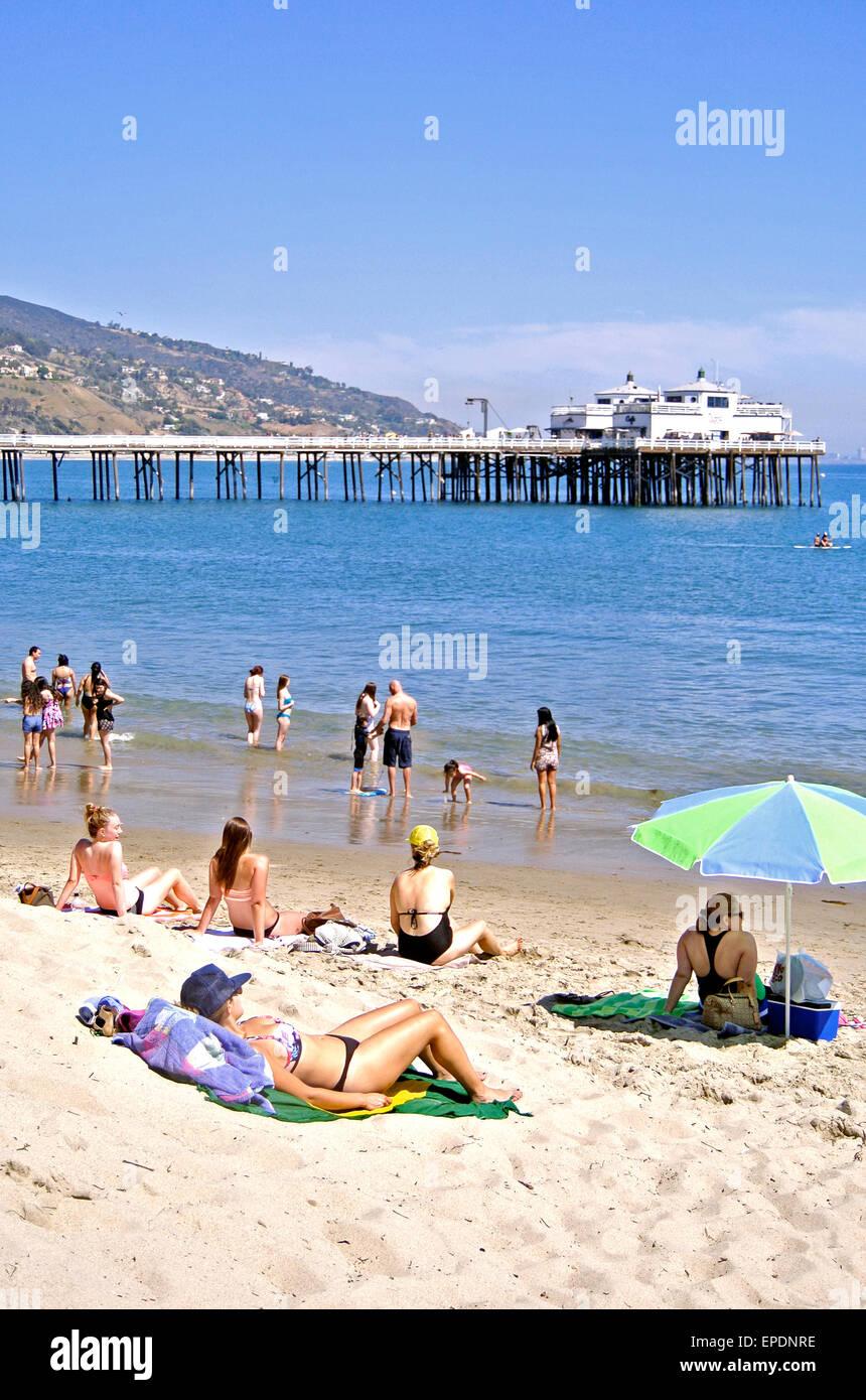 sunbathers relax on sandy Malibu California beach - Stock Image