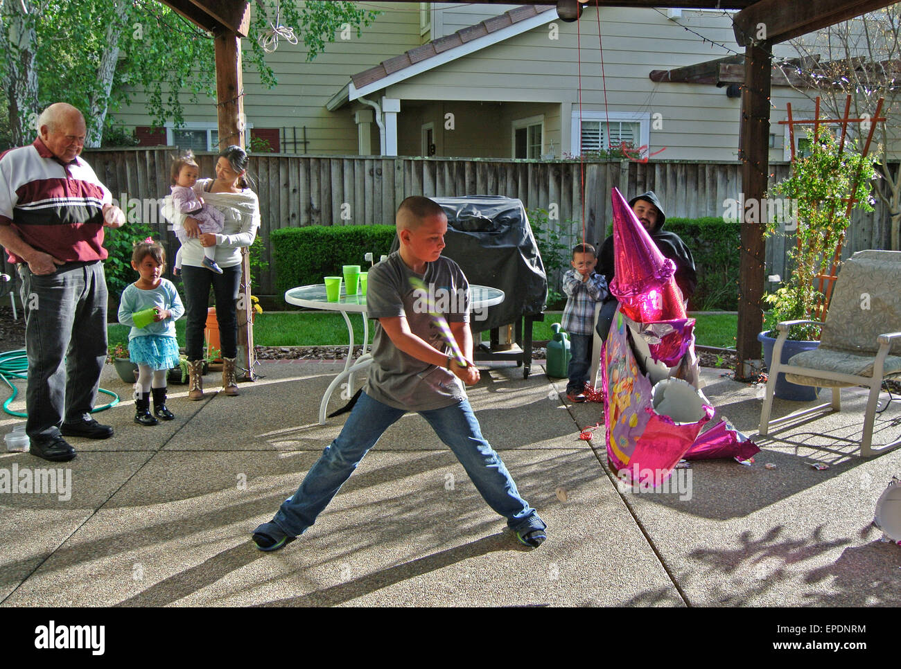 family watches son hit pinata on backyard patio - Stock Image