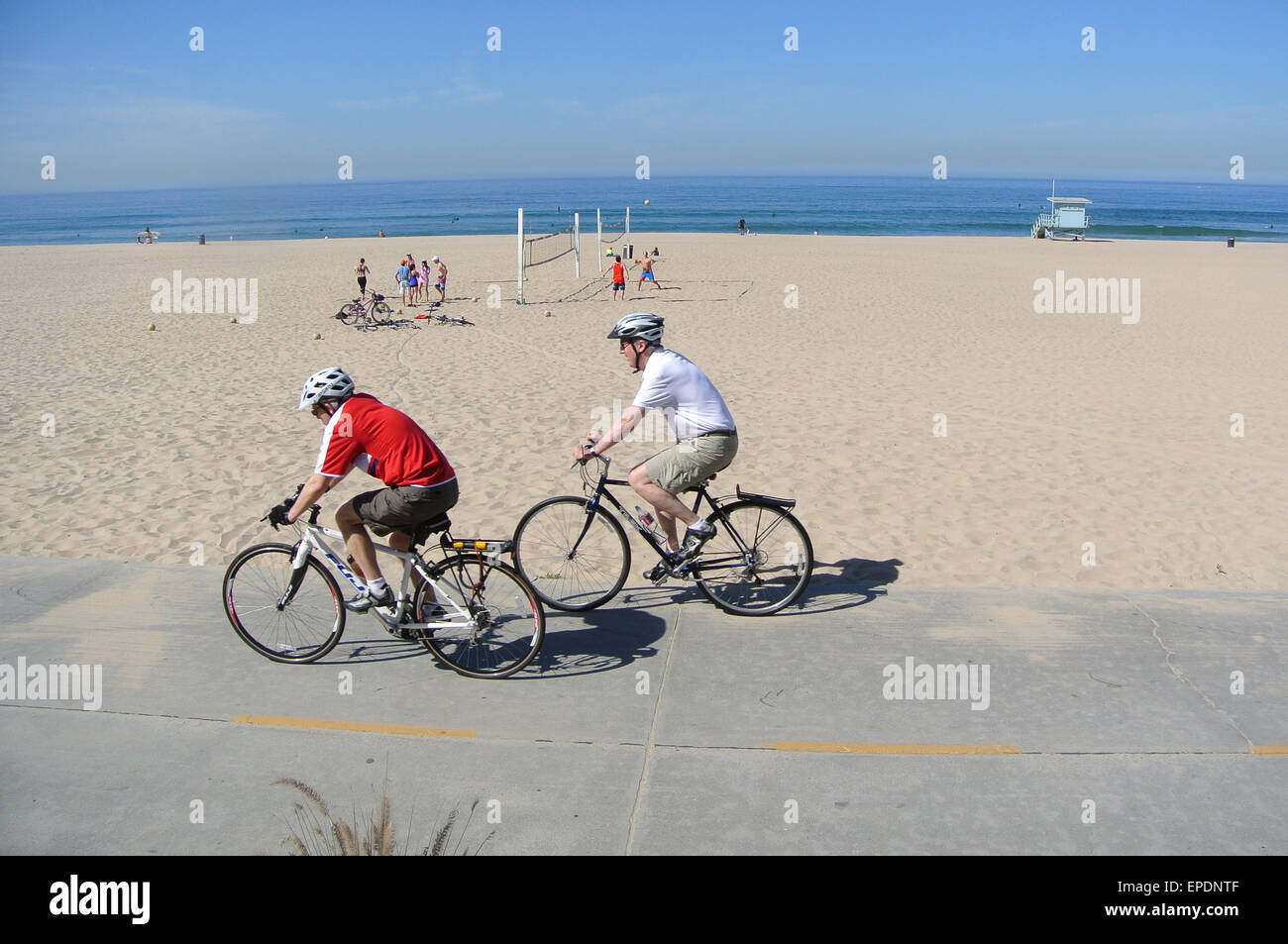 two bicyclists ride on the strand in Manhattan Beach California - Stock Image