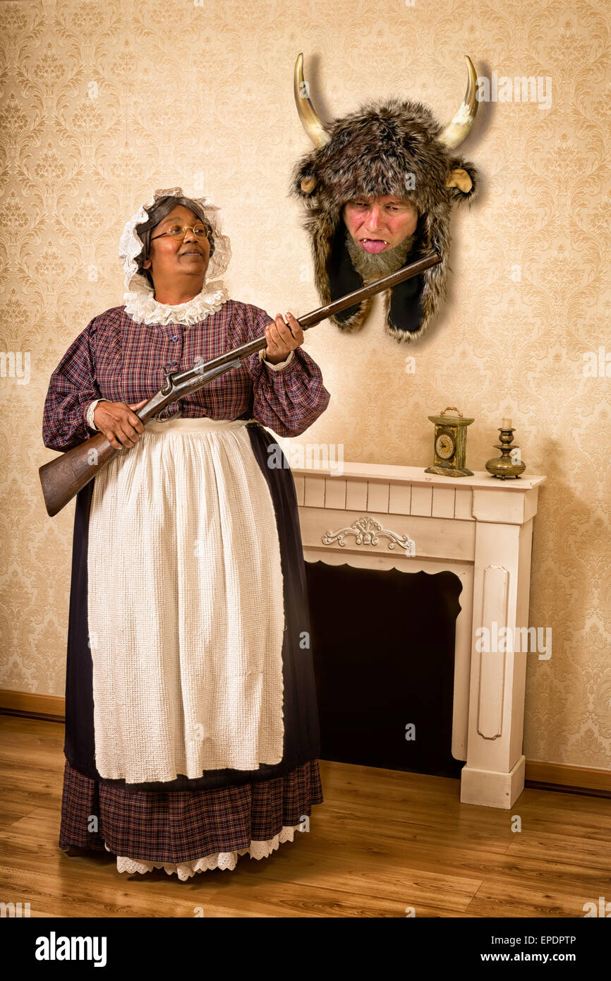 Funny Victorian wife holding a gun in front of her dead husband as a hunting trophy - Stock Image