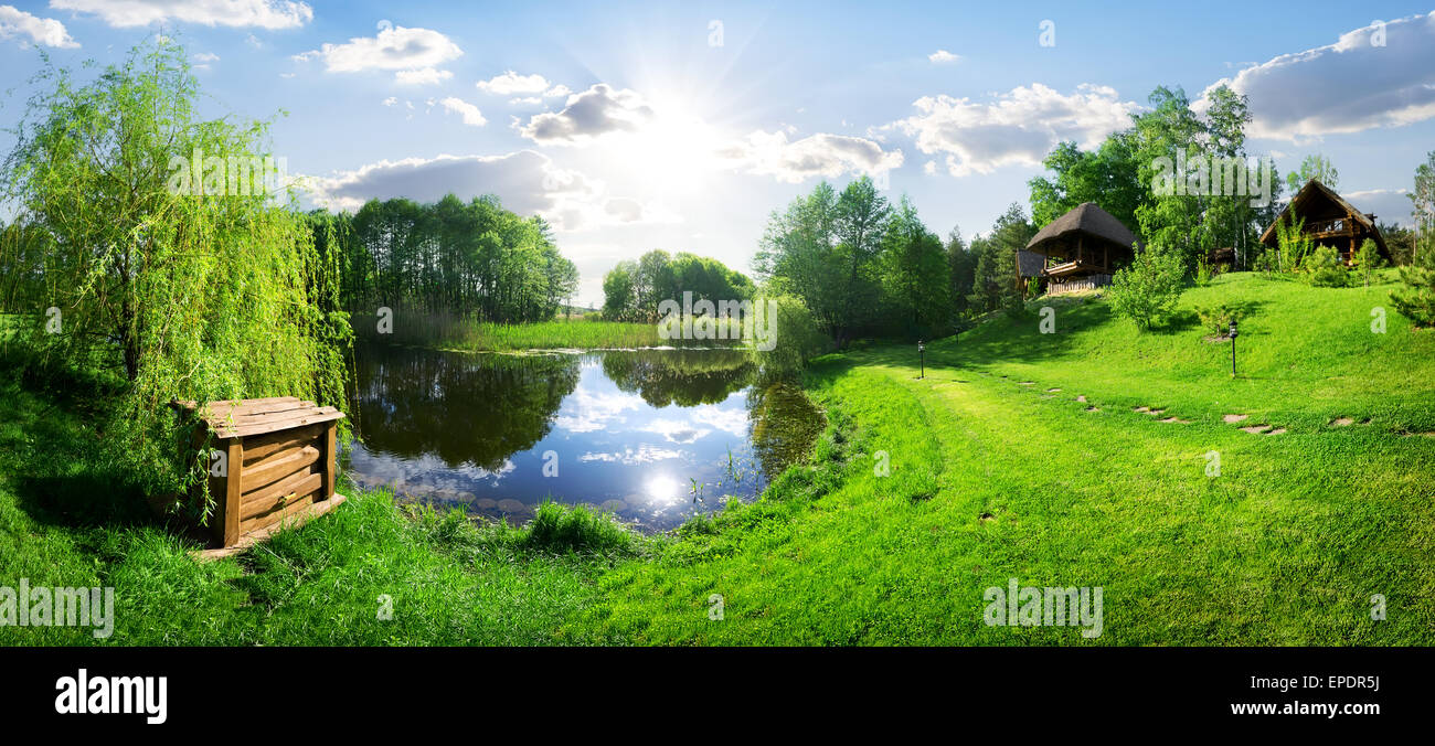 Wooden house near river at sunny day - Stock Image