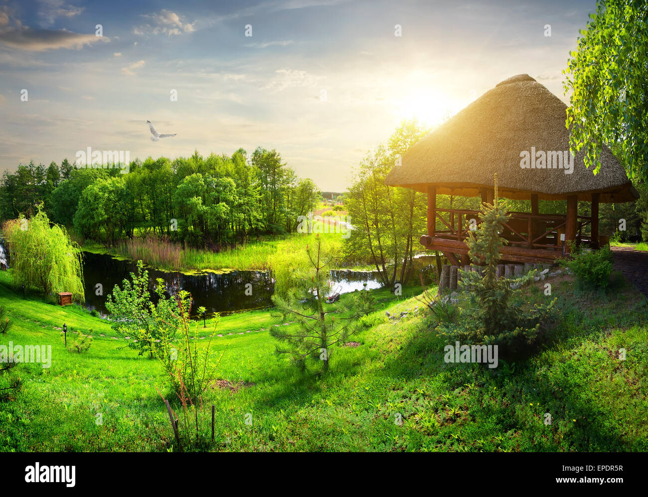 Wooden arbour with thatched roof near river - Stock Image