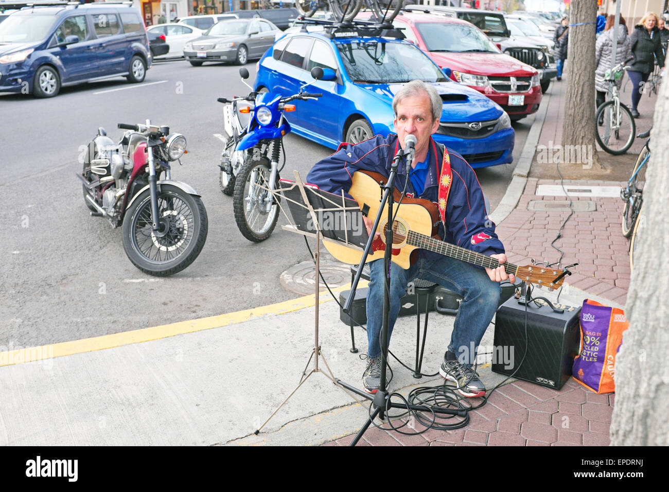 A street musician playing folk songs in downtown Bend, Oregon, during a spring evening - Stock Image