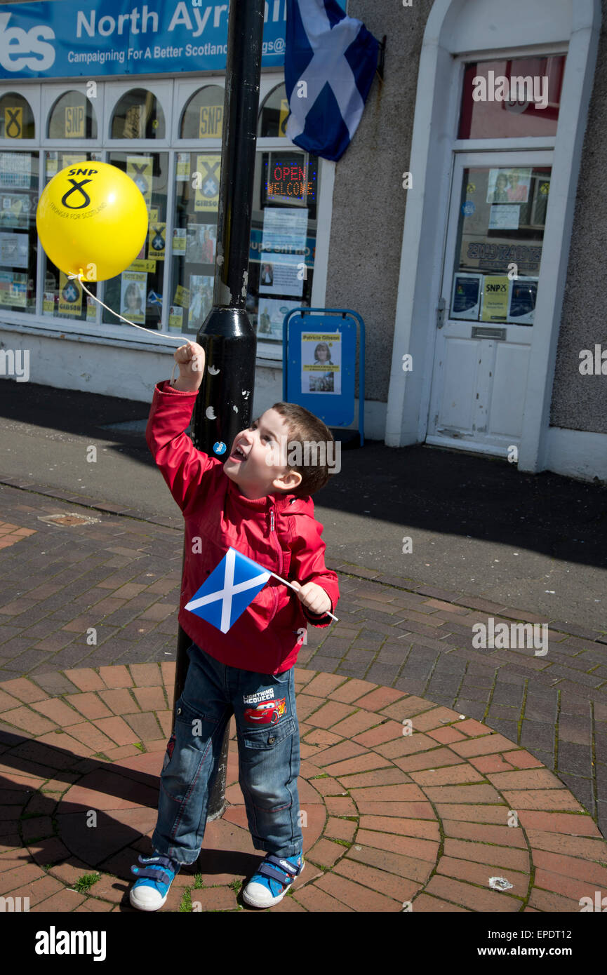 General election 2015. Largs, Ayrshire, Scotland. Small boy with SNP balloon and saltaire (Scottish flag) outside - Stock Image