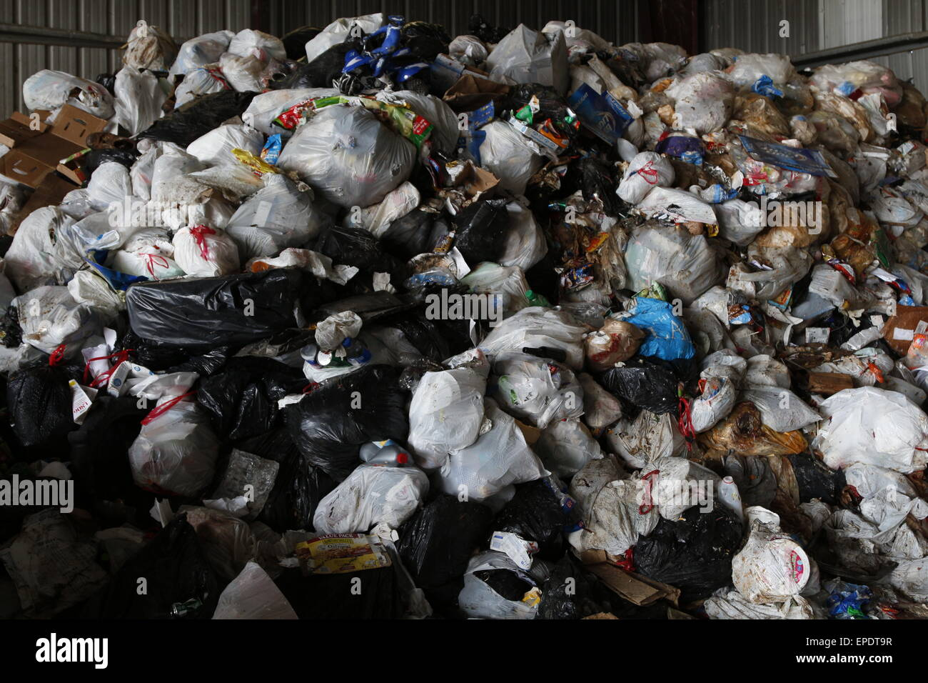 Piles of garbage disposed at a landfill in plastic bags. - Stock Image