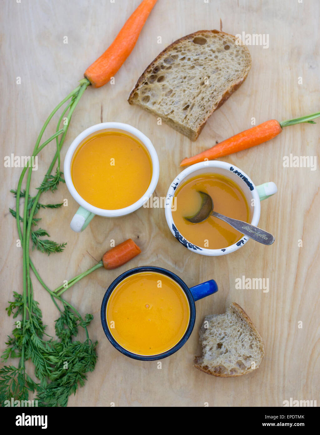 Homemade carrot soup in enamel mugs on a wooden tray with bread and fresh carrots - Stock Image