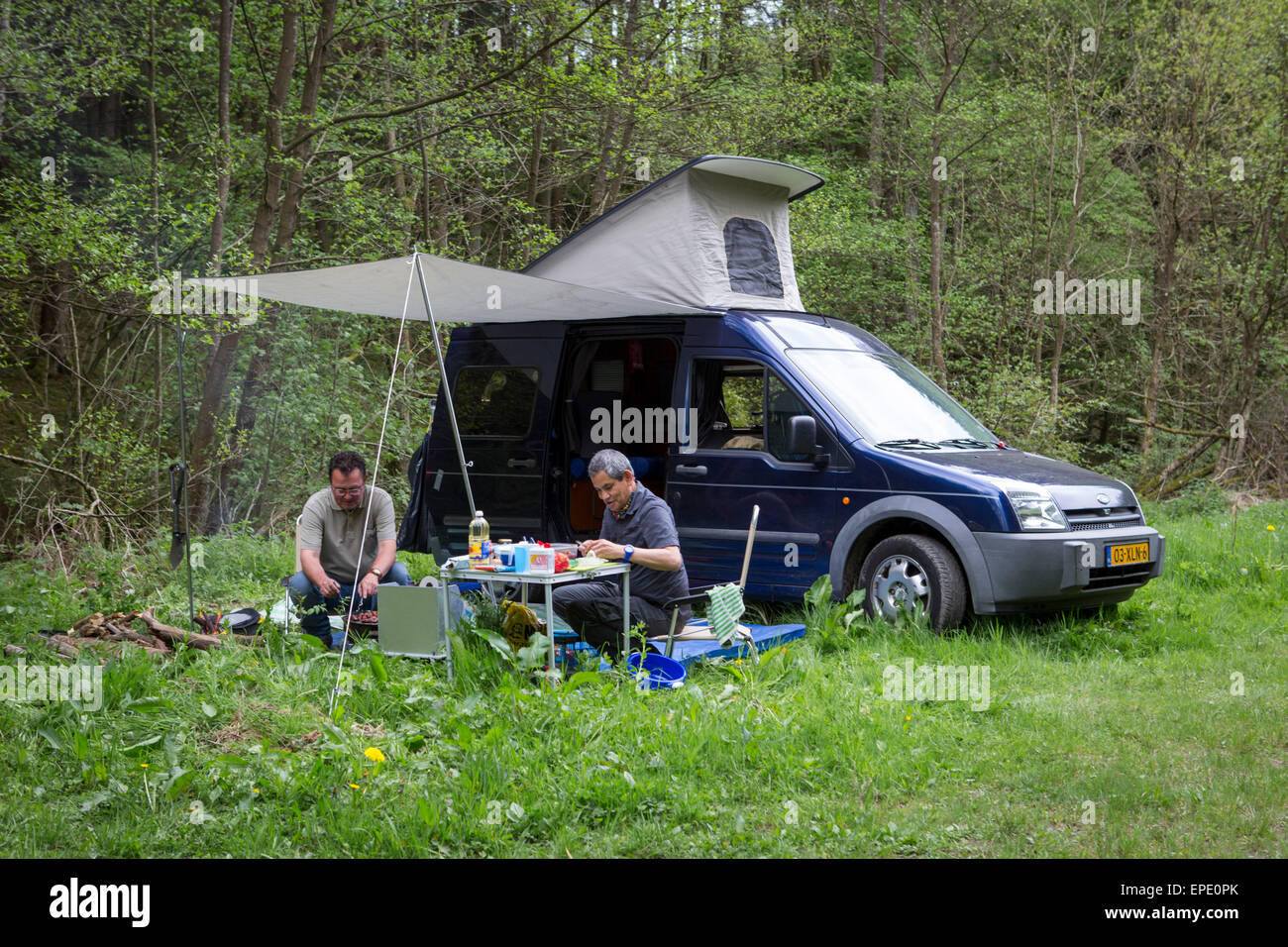 Two Men Cooking And Camping With Their Ford Transit Connect Camper In Stock Photo Alamy
